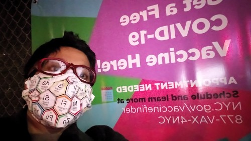 Me, wearing a mask with chemical symbols on it, near a poster saying 'Get a Free COVID-19 Vaccine Here! Appointment needed; schedule and learn more at nyc.gov/vaccinefinder 877-VAX-4NYC'
