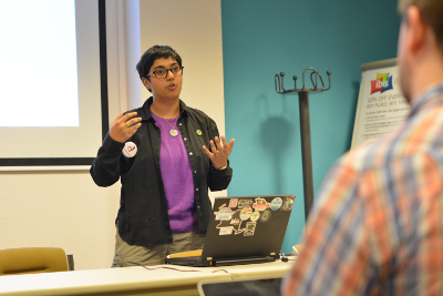 picture of Sumana delivering a talk in front of a  stickered laptop; photo by Ben Vant Ende