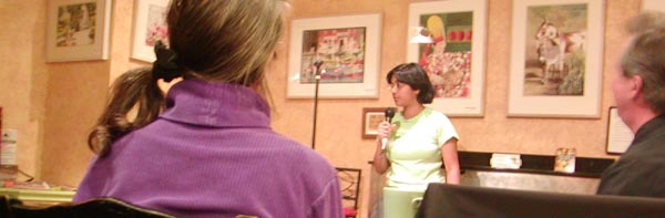 Sumana doing stand-up comedy in a cafe, in front of a few attendees, several years ago